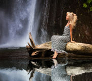 Young woman traveling near the waterfall Royalty Free Stock Image