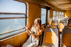 Woman traveling in ferry. Young woman traveling in the old ferry enjoying view on the sea from the window Stock Photo