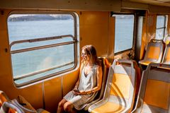 Woman traveling in ferry. Young woman traveling in the old ferry enjoying view on the sea from the window Royalty Free Stock Image