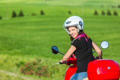 Young woman traveling by a scooter Royalty Free Stock Images