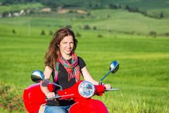 Young woman traveling by a scooter Royalty Free Stock Image
