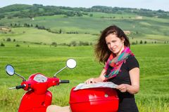 Young woman traveling by a scooter Stock Image
