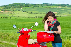 Young woman traveling by a scooter Stock Images