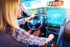 Young woman traveling in self driving car. Young woman traveling in self driving autopilot car or auto Royalty Free Stock Photography