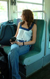 Young woman traveling on train. A young woman sitting on a train looking out the window holding a camera Royalty Free Stock Photo