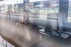 Young woman traveling by train, looking out window while sitting in train. Stock Image