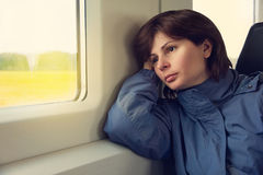 Young woman traveling by train. Young woman is traveling by train, looking to the window Stock Photos