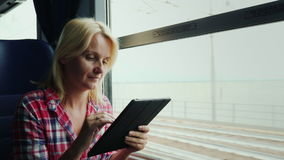A young woman is traveling on a train. Sits by the window, uses a digital tablet. 4K video stock video