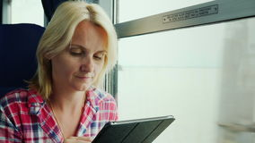 A young woman is traveling on a train. Sits by the window, uses a digital tablet. 4K video stock video footage