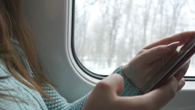 Young woman traveling in a train and using mobile phone. Female hand sends a message from the smartphone. Arm of girl stock video