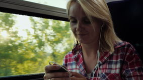 A young woman is traveling on a train using a smartphone. The sun`s rays blink on her face stock video footage