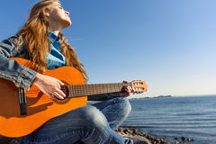 Young woman traveller with guitar outdoor on sea coast Royalty Free Stock Photos