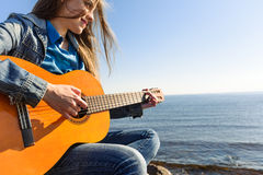 Young woman traveller with guitar outdoor on sea coast Royalty Free Stock Photography