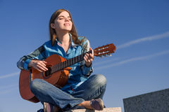 Young woman traveller with guitar outdoor on sea coast Stock Images