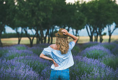 Young woman traveller standing in lavender field, Isparta, Turkey. Young blond curly haired woman traveller wearing straw hat, denim shorts and blue off-shoulder Royalty Free Stock Photo