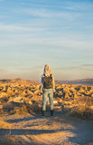 Young woman traveller standing and watching sunrise, Cappadocia, Central Turkey. Young woman traveller wearing hoodie, backpack and jeans standing and watching Royalty Free Stock Images