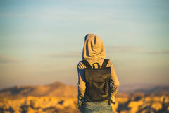 Young woman traveller watching sunrise in Goreme, Cappadocia, Central Turkey. Young woman traveller wearing hoodie and backpack watching sunrise in the mountains Royalty Free Stock Image