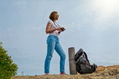 A young woman travels with a backpack and decided to take some photos in a beautiful place. Sky with sun on the backround stock photo