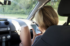 Young woman travels by car and looking for a Navigator on the ph Royalty Free Stock Photo
