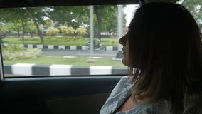 Pretty young woman travels girl is traveling by the car in front of the window. Young woman travels by car and looking out the window and enjoying the view of stock footage