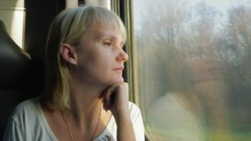 Young woman travels by train, looks out the window at beautiful scenery, dreams. 4K video stock footage