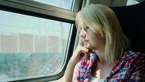 Young woman travels by train, looks out the window, dreams. Portrait of a woman traveling on a train. She looks out the window, sunlight glinting on her face. 4K stock video footage
