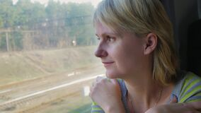 A young woman travels by train, looks out the window at the landscapes. Portrait of a young woman traveling in a train, looking out the window. The sun`s rays stock video footage
