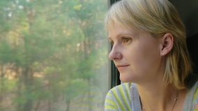 A young woman travels by train, looks out the window at the landscapes. Portrait of a young woman traveling in a train, looking out the window. The sun`s rays stock footage