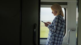 A young woman travels by train, stands by the window, uses a tablet stock video footage