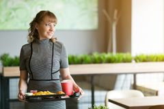 Young woman with a tray of food in a cafe. A woman of 30-35 years old is holding in her hands a dressing on   which juice is water food sushi rolls french fries royalty free stock images