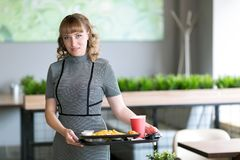 Young woman with a tray of food in a cafe. A woman of 30-35 years old is holding in her hands a dressing on which juice is water food sushi rolls french fries royalty free stock photos