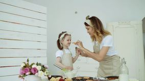 A young woman treats her daughter with pancakes. A woman and a girl bake cookies and muffins. They have a happy family. Mom and little daughter cook together in stock video footage