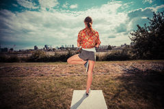 Young woman in tree pose outside Royalty Free Stock Photography