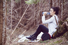 Young woman trekker resting and drinking water Royalty Free Stock Photography