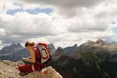 Young woman trekking Dolomite. Young woman resting and checking the map during a trekking at the Dolomite Alps (Italy) with 'Croda da Lago' and 'Cinque Torri' at Royalty Free Stock Photo