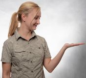Young woman in trekking shirt with open hand looking at it stock photo