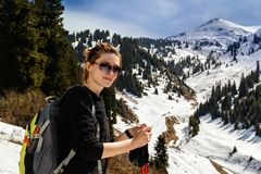 Young woman with trekking sticks in mountainsYoung woman with trekking sticks. Young woman with trekking sticks on the background of mountain peaks Royalty Free Stock Photos