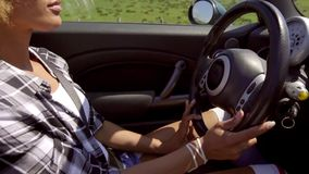 Young woman with a trendy afro hairstyle. Driving her sports car or cabriolet along a rural highway  high angle close up side view stock video