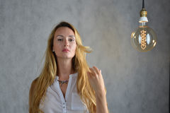 Young woman in a trendy clothes stand between lightbulbs. Unusual art image Royalty Free Stock Photography