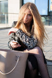 Young woman in a trendy coat  is sitting on the stone parapet in the city Royalty Free Stock Photography