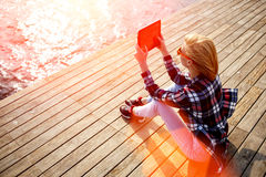 Young woman with trendy look shoot video on digital tablet while sitting on a wooden pier in summer sunny day, Stock Photo