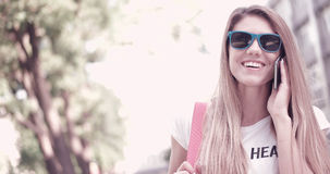Young Woman in Trendy Outfit Smiling while on the phone Stock Image