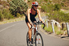 Young woman triathlon athlete cycling. Caucasian female athlete riding cycle on country road Stock Photo