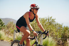 Young woman triathlon athlete cycling on country road Stock Photos