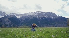 Young woman tries dandelion wreath on herself on mountains background. General plan. Scenic mountain landscape. 4k stock footage