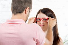 A young woman tries on glasses Stock Photography