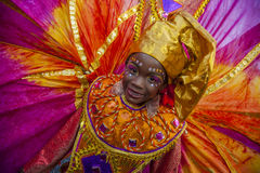 A young woman in Trinidad Carnival masquerade. A brightly clad masquerader in pink, gold and orange with a richly designed color smiles with great joy as she Stock Image