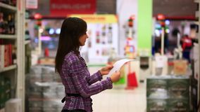 Young woman with trolley checking shopping list at stock video footage