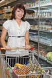 Young woman with a trolley at a supermarket. Beautiful young woman standing with a trolley at a supermarket Stock Photo