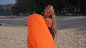 Young woman on a tropical beach inflate an inflatable sofa. Summer vacation concept